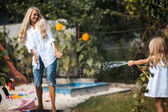 Daughter and mother playing with water — Stock Photo