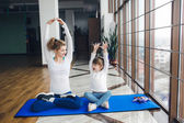 Mother and daughter makeing yoga — Stok fotoğraf