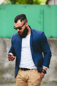 Bearded businessman looking at phone — Stock Photo