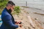 American Bearded Man using phone near the river — Stock Photo
