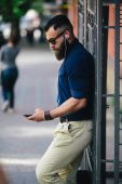 Bearded man standing and listening to music — Stock Photo