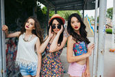 Three beautiful young girls at the bus stop — Stock Photo