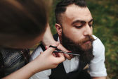 Barber shaves a bearded man — Stock Photo