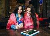 两个女孩坐着听音乐与智能手机 — 图库照片
