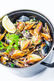 Mussels in saucepan with lemon — Stock Photo