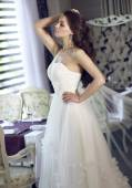Beautiful young bride with long brown wavy hair in a lush white wedding dress of tulle, embroidered with beads corset, bow tied at the waist photographed in the interior of the restaurant — Stock Photo