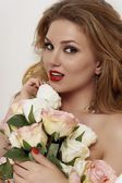Portrait of a young sexy girl with long hair with a bouquet of roses — Stock Photo