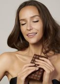 Portrait of a young beautiful girl with dark curly hair, bare shoulders and neck, holding a chocolate bar to enjoy the taste and are dieting, healthy eating and organic foods — Stock Photo