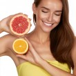 Beautiful sexy young woman with perfect healthy skin and long brown hair day makeup bare shoulders holding orange lemon grapefruit healthy eating organic food diet weight loss — Stock Photo #52700999