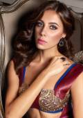 Beautiful sexy brunette woman with wavy hair in a bright multi-colored suit on the wide shoulder straps with rings bracelets accessories, or evening hairstyle and makeup sitting in chair with cushions — Stock Photo