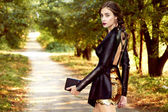 Woman walking in park dressed in lather jacket and gold short — Stock Photo