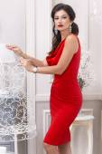 Beautiful sexy luxurious well-groomed young woman in a red slinky dress earrings with diamonds and watches long black hair standing in an interior with white walls — Stok fotoğraf