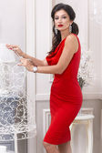 Beautiful sexy luxurious well-groomed young woman in a red slinky dress earrings with diamonds and watches long black hair standing in an interior with white walls — Stockfoto