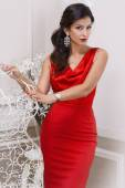 Beautiful sexy luxurious well-groomed young woman in a red slinky dress earrings with diamonds and watches long black hair standing in an interior with white walls — Stock Photo