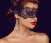 Young beautiful sexy woman with dark lace on eyes bare shoulders and neck, jewelry earrings, feeling temptation, passion sex red lips — Stock Photo