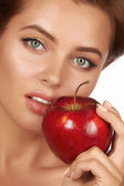 Young beautiful sexy girl with dark curly hair, bare shoulders and neck, holding big red apple to enjoy the taste and are dieting, healthy eating and organic foods, feeling temptation, smile, teeth — Stock Photo