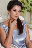 Sexy beautiful young brunette woman with evening make-up chic groomed wearing a short evening dress embroidered with silver sequins and earrings sitting on the couch in background with flower — Stock Photo