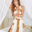 Beautiful sexy young blonde woman with long curly hair and make-up wearing a long evening dress white with gold embroidery and jewelery and accessories in bedroom is going to a party or red carpet — Stock Photo #55668467