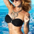 Beautiful blonde or red girl with perfect tan skin with golden big necklace on the neck staying in wet black swimming suite and brown sunglasses inside of water in swimming pool with light blue water — Stock Photo #55668483