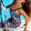 Beautiful blonde girl with pink lips and perfect tan skin in colorful summer wet dress siting on the wood floor near swimming pool with light blue water smiling and holding for a handrail of the pool — Stock Photo #55668827