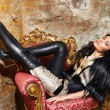 Beautiful sexy woman long brunette hair in black fur Treads on high heel gold pans sitting on the chair red brick wall background makeup fashion style — Stock Photo #55669461