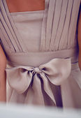 Detail on clothing or large silk chiffon bow on a beige dress — Stock Photo