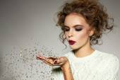 Beautiful girl with evening makeup blow gold sequins  — Stock Photo