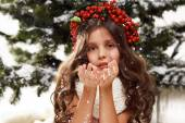 Beautiful little girl sitting in the snow at Christmas trees  — Photo