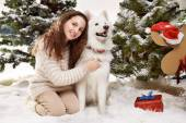 Beautiful little girl sitting in the snow at Christmas trees — Stock Photo
