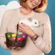 Beautiful woman holding white little Easter bunny basked eggs — Stock Photo #60952517