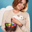 Beautiful woman holding white little Easter bunny basked eggs — Stock Photo #60952525