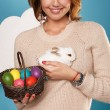 Beautiful woman holding white little Easter bunny basked eggs — Stock Photo #60952537