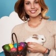 Beautiful woman holding white little Easter bunny basked eggs — Stock Photo #60952541