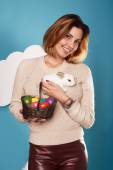 Beautiful woman holding white little Easter bunny basked eggs — Stock Photo