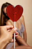 Lovely woman smiling covers one eye lollipop red hear — Stock Photo