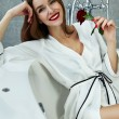Sexy woman in bathroom in silk robe rose Valentine's day — Stock Photo #62608361