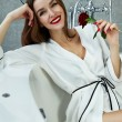 Sexy woman in bathroom in silk robe rose Valentine's day — Stock Photo #62608419
