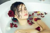 Beautiful sexy woman takes bath rose candles Valentine's day spa — Stock Photo
