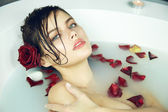 Beautiful young sexy woman with dark hair wet, evening makeup, takes bath with milk and rose petals and candles, beauty salon and spa Valentine — Zdjęcie stockowe