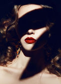 Beautiful blonde curly hair makeup red lips in the shadows — Stock Photo