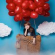 Small cute girl flying on red heart balloons Valentines day — Stock Photo #64095697