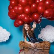 Small cute girl flying on red heart balloons Valentines day — Stock Photo #64095749