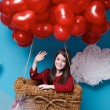 Small cute girl flying on red heart balloons Valentines day — Stock Photo #64095757