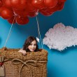 Small cute girl flying on red heart balloons Valentines day — Stock Photo #64095911