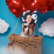 Small cute girl flying on red heart balloons Valentines day — Stock Photo #64095993