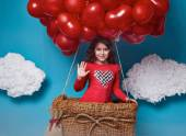 Small cute girl flying on red heart balloons Valentines day — Zdjęcie stockowe