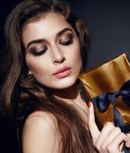Beautiful sexy woman brunett evening makeup with box present — Stock Photo