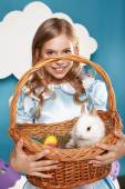 Little girl with basket with color eggs and white Easter bunny — Stock Photo