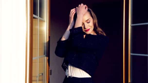 Beautiful sexy young woman with blond hair coming out of the door flirting shy sends kiss breathe air free air, perfume, cosmetics, make-up and party sun shining — Vídeo de stock