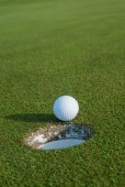 Golf Ball about to go in the hole — Stock Photo